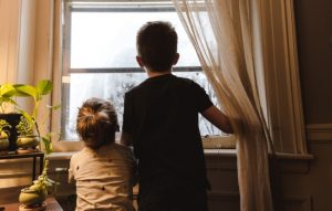 Two siblings looking outside a window